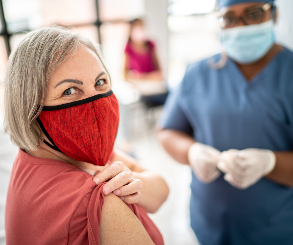 women wearing mask with bandage on arm after vaccine